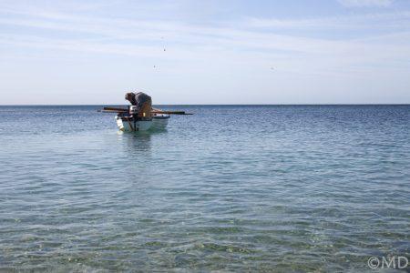 Local pot fisherman preparing boat at Chesil Cove, Dorset, UK
